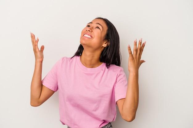 Giovane donna latina isolata su sfondo bianco che urla al cielo, alzando lo sguardo, frustrata. Foto Premium