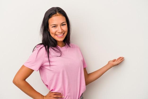Giovane donna latina isolata su sfondo bianco che mostra un'espressione di benvenuto.