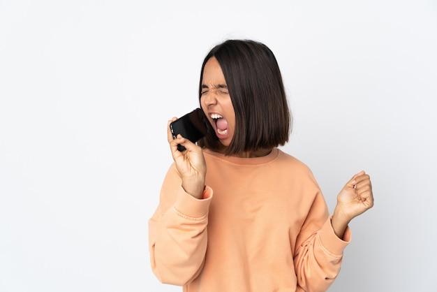 Giovane donna latina isolata sul muro bianco utilizzando il telefono cellulare e cantando