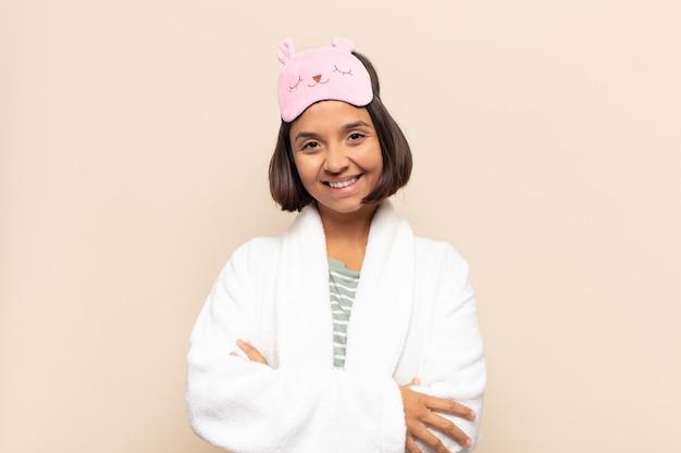 Giovane donna latina che ride felice con le braccia incrociate, con una posa rilassata, positiva e soddisfatta
