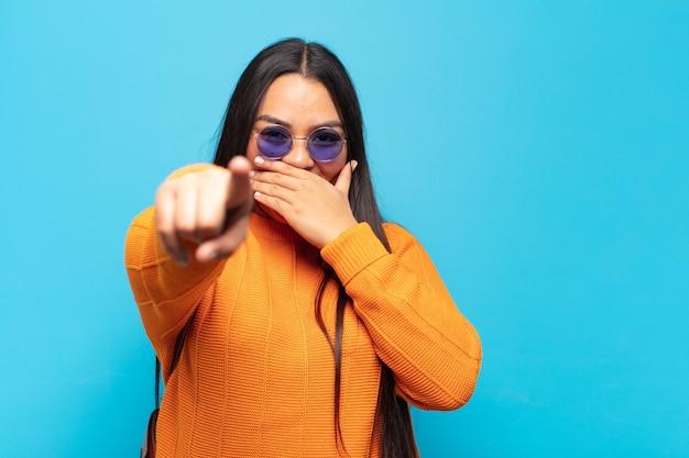 Giovane donna latina che ride di te, indica la telecamera e ti prende in giro o ti prende in giro