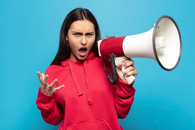 Giovane donna latina che sembra arrabbiata, irritata e frustrata che grida wtf o cosa c'è di sbagliato in te