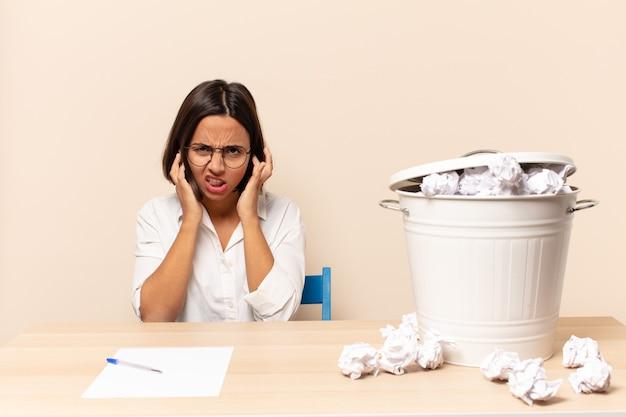 Giovane donna latina che sembra arrabbiata, stressata e infastidita, coprendo entrambe le orecchie con un rumore assordante, un suono o una musica ad alto volume