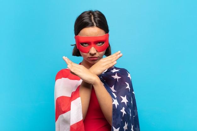 Giovane donna latina che sembra infastidita e stanca del tuo atteggiamento, dicendo basta! mani incrociate davanti, dicendoti di fermarti