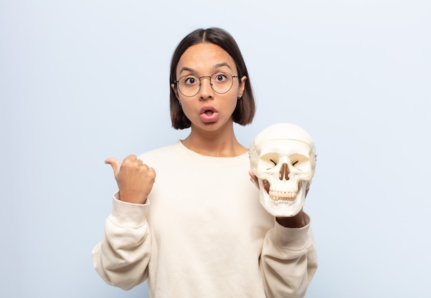 Giovane donna latina che guarda stupita incredula, indicando un oggetto sul lato e dicendo wow, incredibile