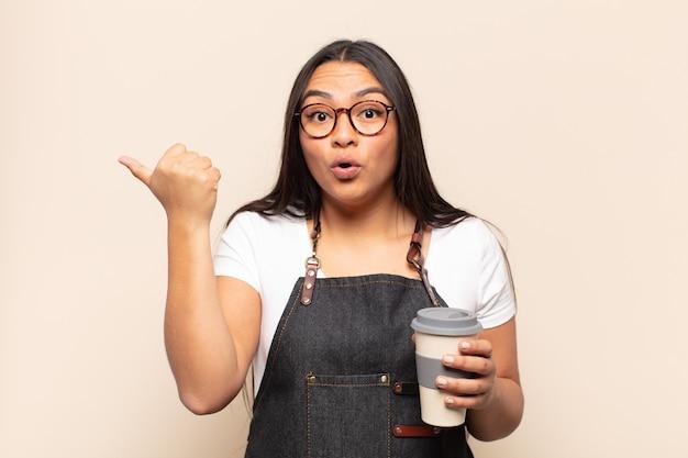 Giovane donna latina che sembra stupita per l'incredulità, indicando un oggetto sul lato e dicendo wow, incredibile