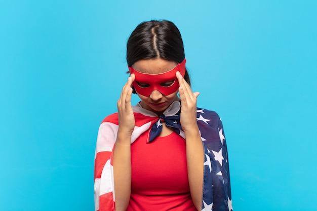 Giovane donna latina che sembra concentrata, premurosa e ispirata, fa brainstorming e immagina con le mani sulla fronte