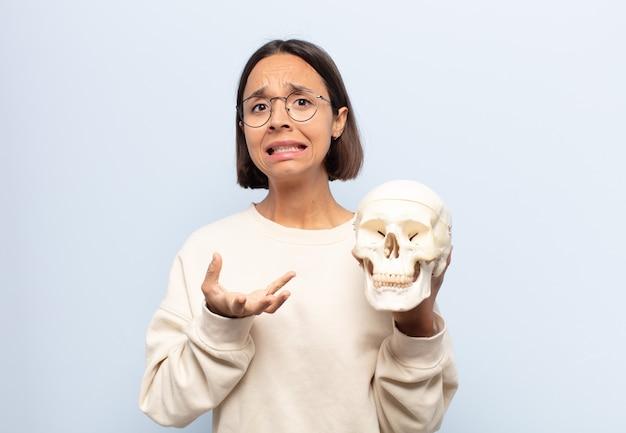Giovane donna latina che sembra disperata e frustrata, stressata, infelice e infastidita, urla e urla Foto Premium