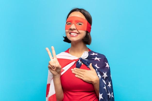 Giovane donna latina che sembra felice, sicura e degna di fiducia, sorridente e mostrando segno di vittoria, con un atteggiamento positivo