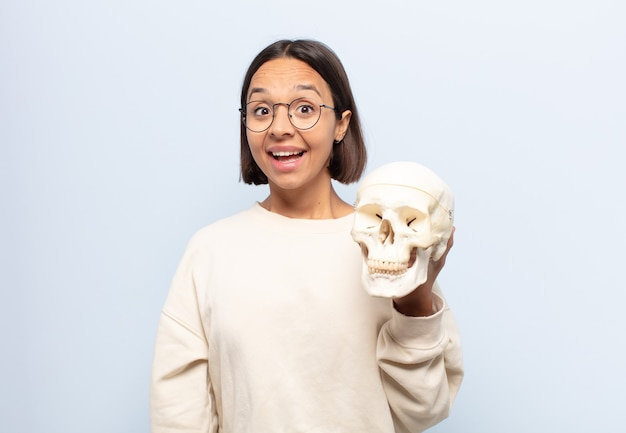 Giovane donna latina che sembra felice e piacevolmente sorpresa, eccitata da un'espressione affascinata e scioccata
