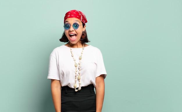 Giovane donna latina che sembra felice e piacevolmente sorpresa, eccitata con un'espressione affascinata e scioccata