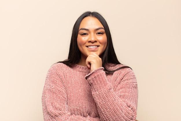 Giovane donna latina che sembra felice e sorridente con la mano sul mento, chiedendosi o facendo una domanda, confrontando le opzioni