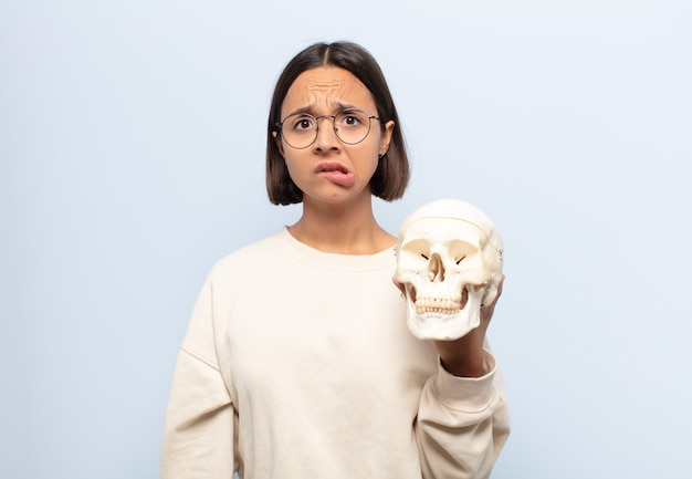 Giovane donna latina che sembra perplessa e confusa, mordendosi il labbro con un gesto nervoso, non conoscendo la risposta al problema