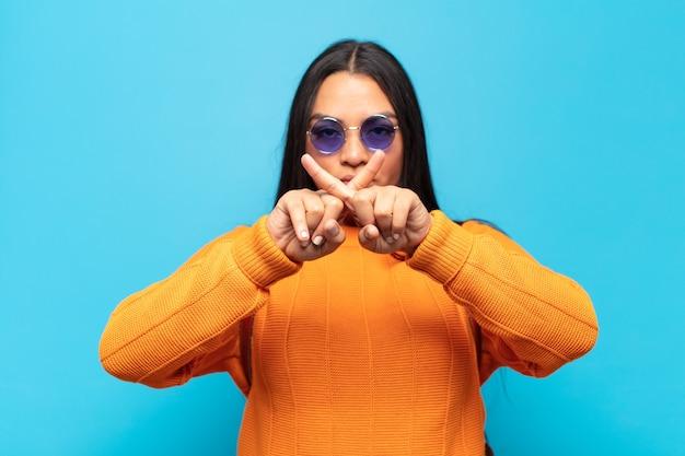 Giovane donna latina dall'aria seria e scontenta con entrambe le dita incrociate davanti in segno di rifiuto, chiedendo silenzio