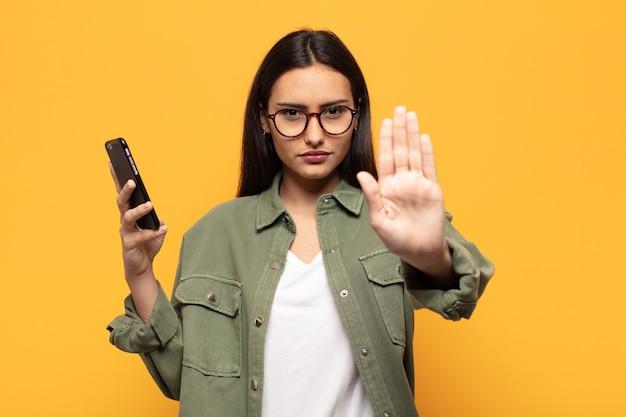 Giovane donna latina che sembra seria, severa, dispiaciuta e arrabbiata che mostra il palmo aperto che fa il gesto di arresto