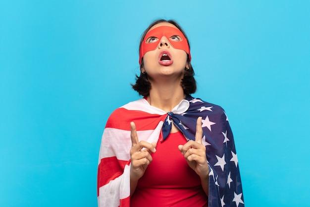 Giovane donna latina che sembra scioccata, stupita e con la bocca aperta, rivolta verso l'alto con entrambe le mani per copiare lo spazio
