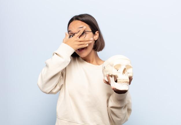 Giovane donna latina che sembra scioccata, spaventata o terrorizzata, coprendosi il viso con la mano e sbirciando tra le dita
