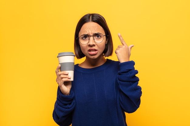 Giovane donna latina che sembra sorpresa, a bocca aperta, scioccata, realizzando un nuovo pensiero, idea o concetto