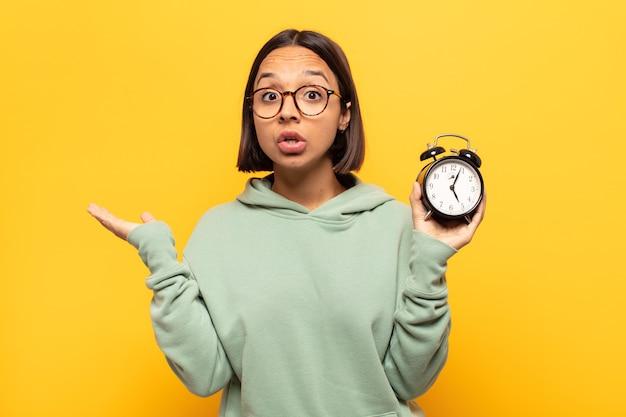 Giovane donna latina che sembra sorpresa e scioccata, con la mascella caduta tenendo un oggetto con una mano aperta sul lato