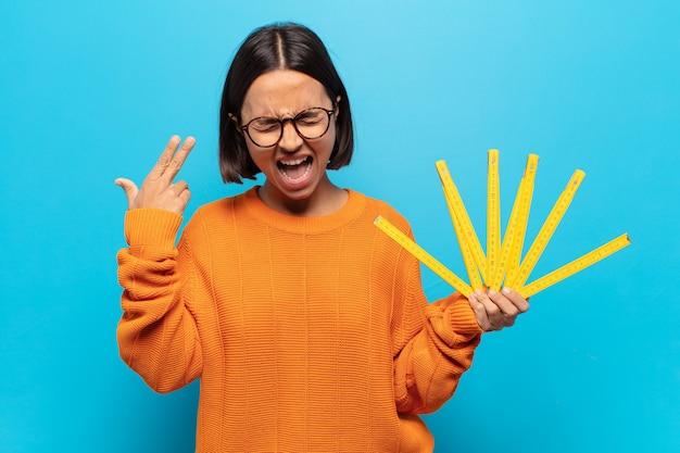 Giovane donna latina che sembra infelice e stressata, gesto suicida che fa il segno della pistola con la mano, indicando la testa
