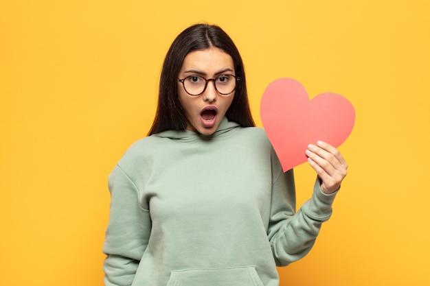 Giovane donna latina che sembra molto scioccata o sorpresa, fissando con la bocca aperta dicendo wow