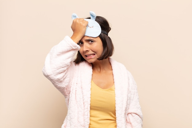 Giovane donna latina che alza il palmo alla fronte pensando oops, dopo aver commesso uno stupido errore o ricordando, sentendosi stupida
