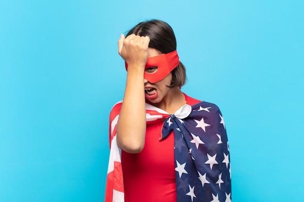 Giovane donna latina che alza il palmo alla fronte pensando oops, dopo aver commesso uno stupido errore o aver ricordato