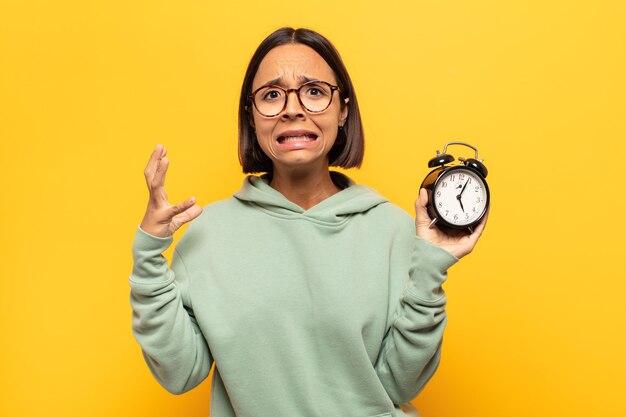 Giovane donna latina che grida con le mani in alto, sentendosi furiosa, frustrata, stressata e sconvolta