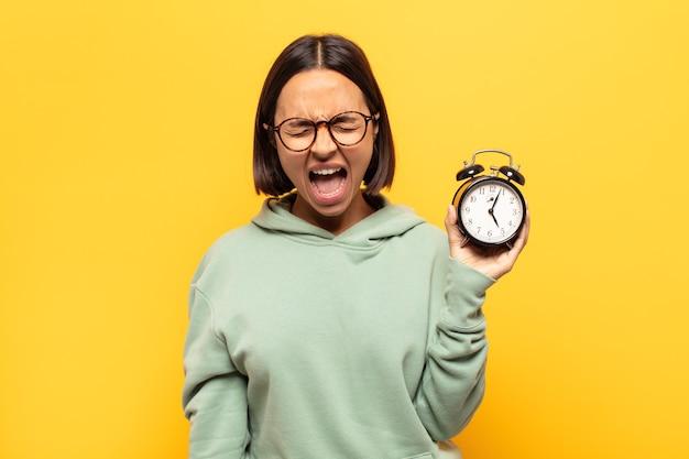 Giovane donna latina che grida in modo aggressivo, sembra molto arrabbiata, frustrata, indignata o infastidita, grida di no