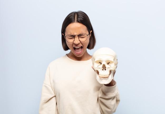 Giovane donna latina che grida in modo aggressivo, sembra molto arrabbiata, frustrata, oltraggiata o infastidita, grida di no