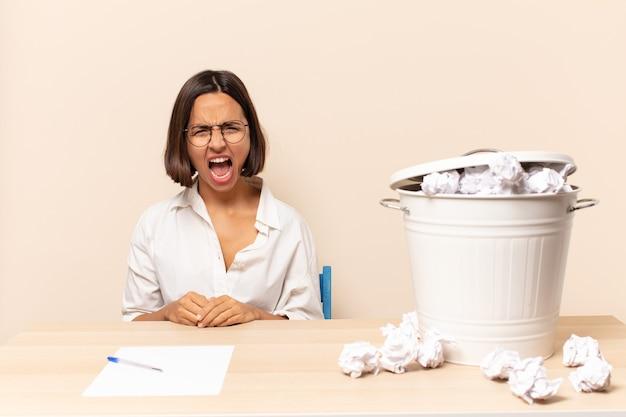 Giovane donna latina che grida in modo aggressivo, sembra molto arrabbiata