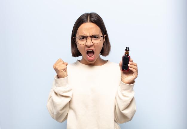 Giovane donna latina che grida in modo aggressivo con un'espressione arrabbiata o con i pugni chiusi per celebrare il successo