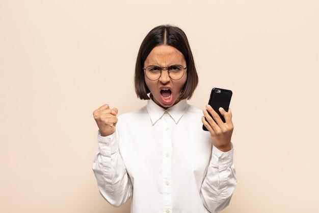 Giovane donna latina che grida in modo aggressivo con un'espressione arrabbiata o con i pugni chiusi celebrando il successo