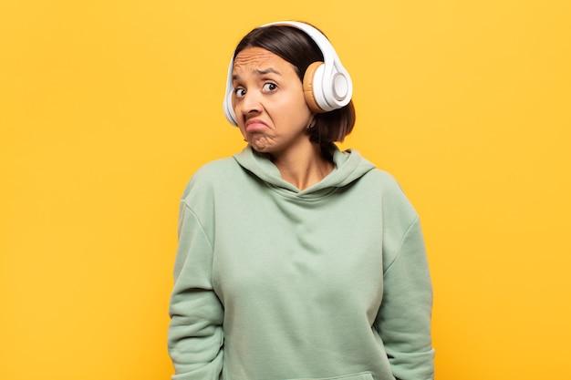 Giovane donna latina che scrolla le spalle, sentendosi confusa e incerta, dubbiosa con le braccia incrociate e lo sguardo perplesso