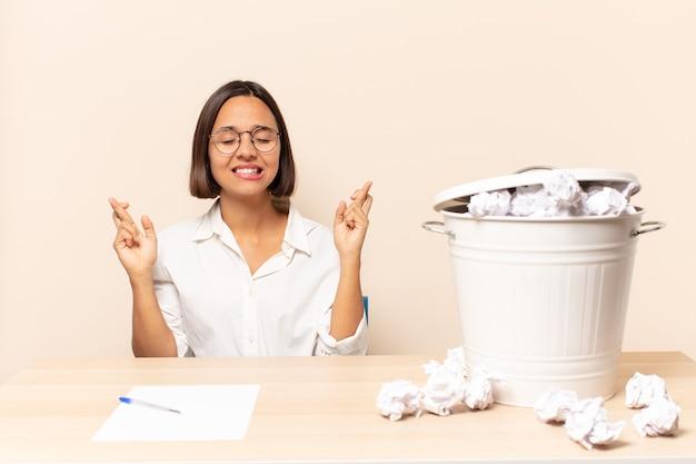 Giovane donna latina che sorride e incrocia ansiosamente entrambe le dita, si sente preoccupata e desidera o spera in buona fortuna