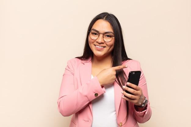 Giovane donna latina che sorride allegramente, sentendosi felice e indicando il lato e verso l'alto, mostrando l'oggetto nello spazio della copia