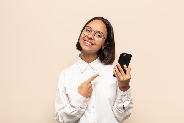 Giovane donna latina che sorride allegramente, si sente felice e indica di lato e verso l'alto, mostrando l'oggetto nello spazio della copia