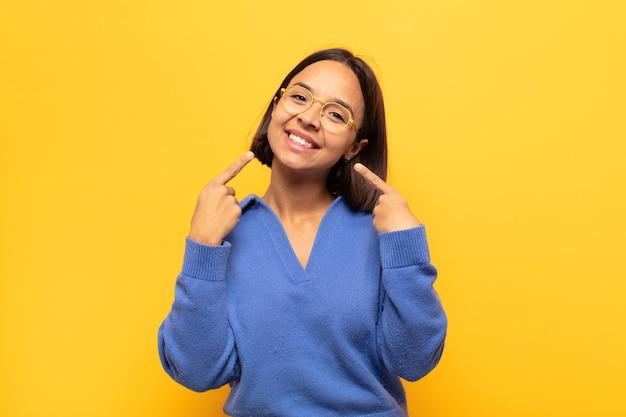 Giovane donna latina che sorride fiduciosamente indicando il proprio ampio sorriso, atteggiamento positivo, rilassato e soddisfatto