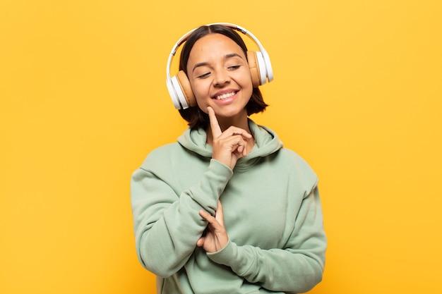 Giovane donna latina sorridente felicemente e fantasticando o dubitando, guardando al lato