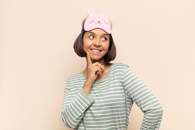 Giovane donna latina che sorride felice e sogna ad occhi aperti o dubita, guardando di lato