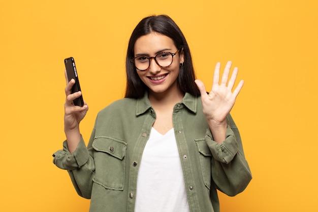 Giovane donna latina che sorride e sembra amichevole, mostrando il numero cinque o quinto con la mano in avanti, conto alla rovescia