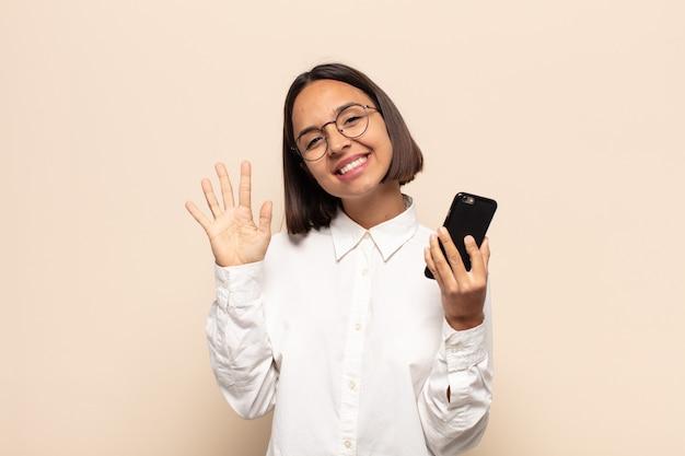 Giovane donna latina che sorride e sembra amichevole, mostrando il numero cinque o quinto con la mano in avanti, contando alla rovescia
