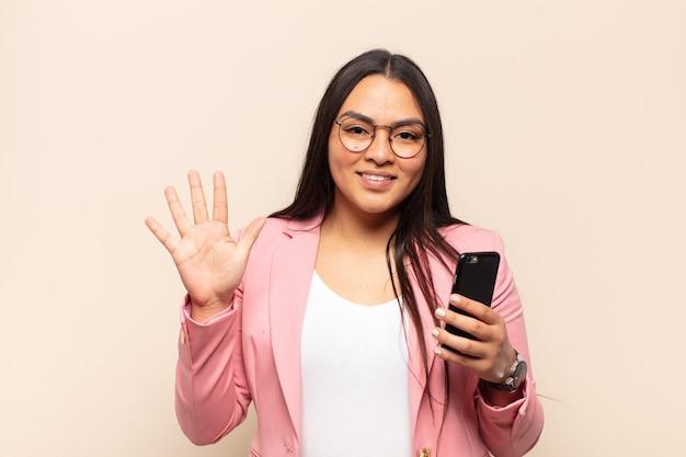 Giovane donna latina sorridente e dall'aspetto amichevole, mostrando il numero cinque o il quinto con la mano in avanti, conto alla rovescia