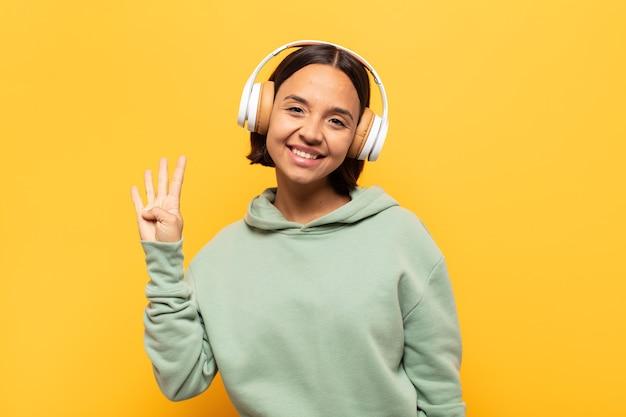 Giovane donna latina che sorride e sembra amichevole, mostrando il numero quattro o quarto con la mano in avanti, contando alla rovescia