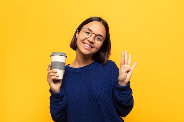 Giovane donna latina sorridente e dall'aspetto amichevole, mostrando il numero quattro o il quarto con la mano in avanti, conto alla rovescia