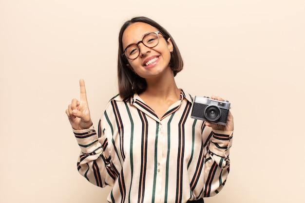 Giovane donna latina che sorride e sembra amichevole, mostrando il numero uno o il primo con la mano in avanti, contando alla rovescia