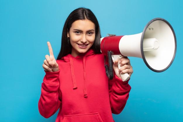 Giovane donna latina che sorride e sembra amichevole, mostrando il numero uno o prima con la mano in avanti, conto alla rovescia