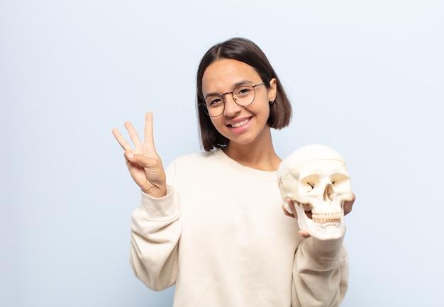 Giovane donna latina che sorride e sembra amichevole, mostrando il numero tre o terzo con la mano in avanti, contando alla rovescia