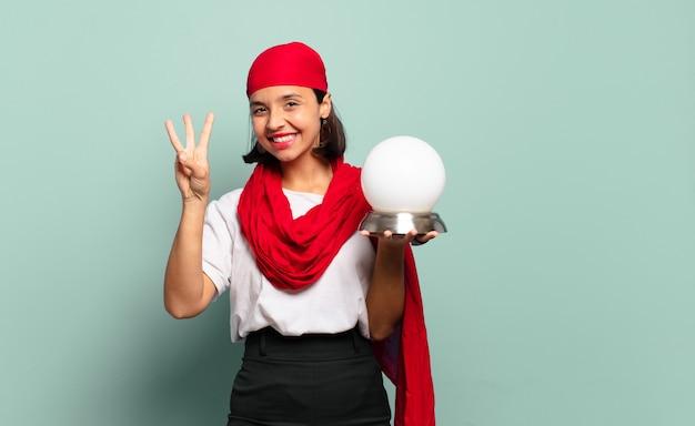 Giovane donna latina che sorride e sembra amichevole, mostrando il numero tre o terzo con la mano in avanti, conto alla rovescia