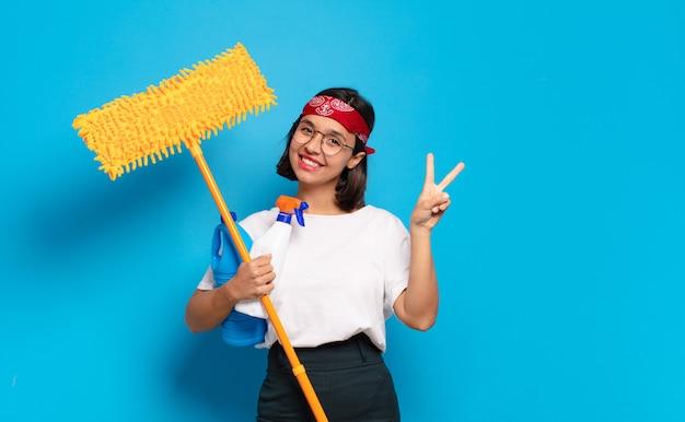Giovane donna latina che sorride e sembra amichevole, mostrando il numero due o il secondo con la mano in avanti, il conto alla rovescia